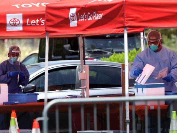 अमेरिका के लॉस एंजिल्स स्थित बैंक ऑफ कैलिफोर्निया की पार्किंग में बने एक टेस्टिंग सेंटर पर काम करते स्वास्थ्यकर्मी।