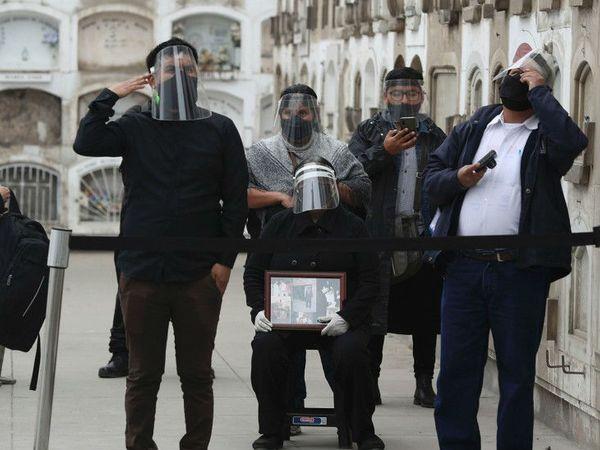 पेरू के लीमा में संक्रमित व्यक्ति के अंतिम संस्कार में प्रोटेक्टिव गियर्स पहनकर शामिल होते परिजन।