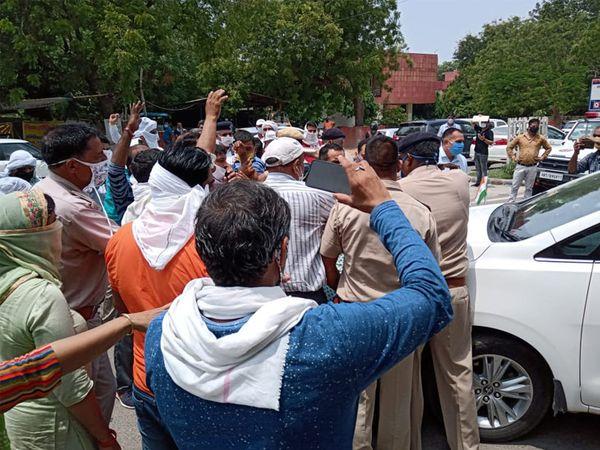 गाड़ी से लिपटे पीटीआई शिक्षकों को हटाते हुए पुलिस।