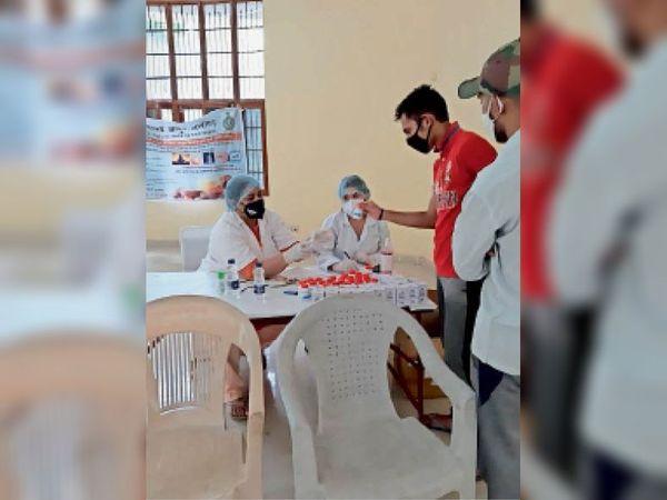 कोरोना से बचाव के लिए आयुर्वेदिक दवाइयां वितरित करते स्वास्थ्य कर्मी। - Dainik Bhaskar