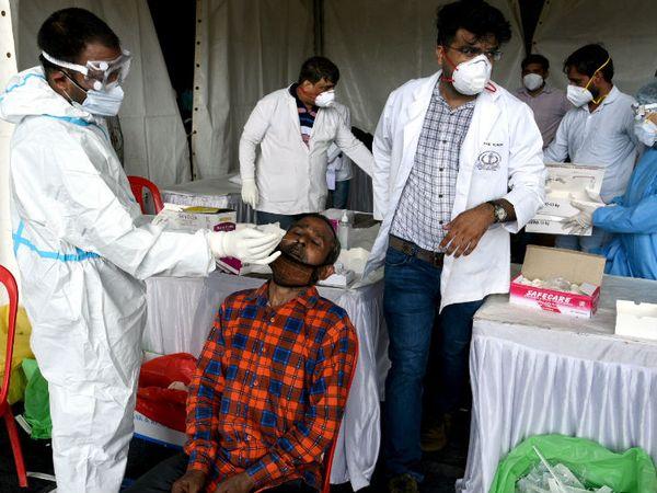 नई दिल्ली के आनंद विहार बस टर्मिनल पर हेल्थ केयर वर्कर्स यहां लौटने वाले मजदूरों का स्वैब सैम्पल लेते हुए। देश के अळग-अळग हिस्सों से मजदूर काम के लिए फिर से लौटने लगे हैं। - Dainik Bhaskar