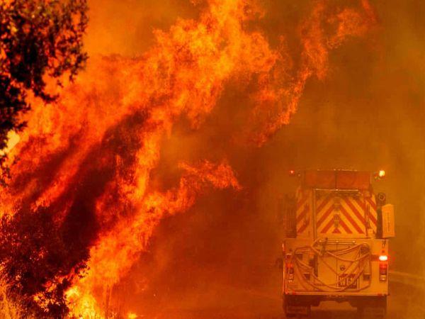 नापा काउंटी में बुधवार को आग की तेज लपटों के बीच जाता फायर डिपार्टमेंट का ट्रक।