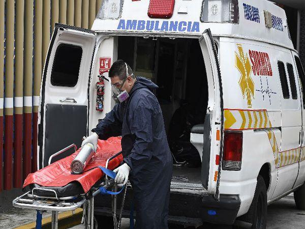 मैक्सिको की राजधानी न्यू मैक्सिको सिटी में गुरुवार को मरीज को पहुंचाने के बाद सामान सहेजने में जुटा एंबुलेंस स्टाफ।