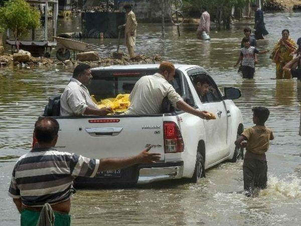 कराची के एक इलाके में खुली कार से लोगों के बीच खाने-पीने का सामान बांटते एनजीओ के वालंटियर्स। सोर्स- डॉन
