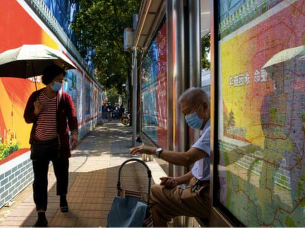बुधवार को चीन की राजधानी बीजिंग में अपने घर के बाहर मौजूद बुजुर्ग। चीन में बुधवार को 11 नए केस सामने आए। सभी संक्रमित दूसरे देशों से चीन आए थे।
