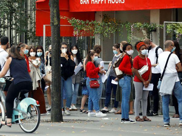 फ्रांस की राजधानी पेरिस में एक कैफे के बाहर मास्क लगाकर खड़े लोग। फ्रांस ने संक्रमण रोकने के लिए पब्लिक प्लेस पर मास्क पहनना जरूरी कर दिया है।
