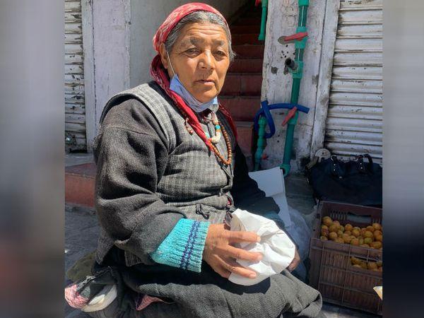 लेह मार्केट में कुछ सामान लेकर बैठी हुई महिला। जब से चीन सीमा पर गोली चली है यहां के रहवासियों को युद्ध का डर सता रहा है।