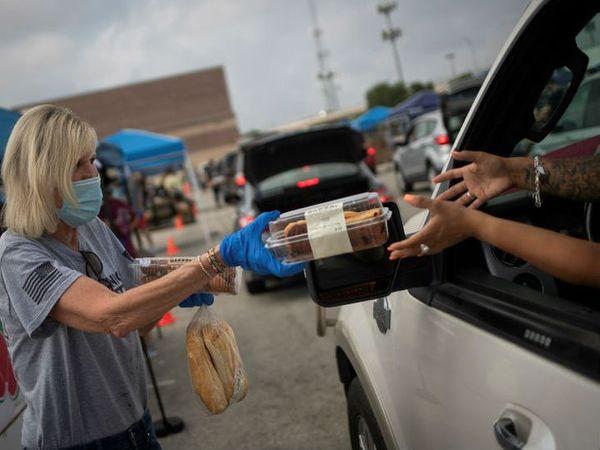 अमेरिका के टेक्सास में कोरोना महामारी में फूड बैंक के लोग खाना बांटते हुए। -फाइल फोटो
