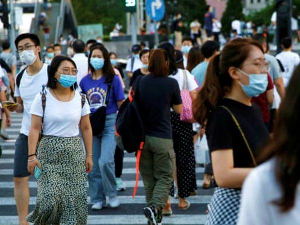 रविवार को बीजिंग में मास्क लगाकर घूमते लोग। चीन में रविवार को 10 मामले सामने आए थे। सोमवार को 8 मामले सामने आए। सभी संक्रमित दूसरे देशों से चीन लौटे थे।