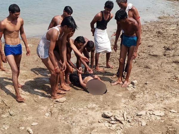 स्थानीय लोगों ने एक महिला की लाश नदी से बाहर निकाली।