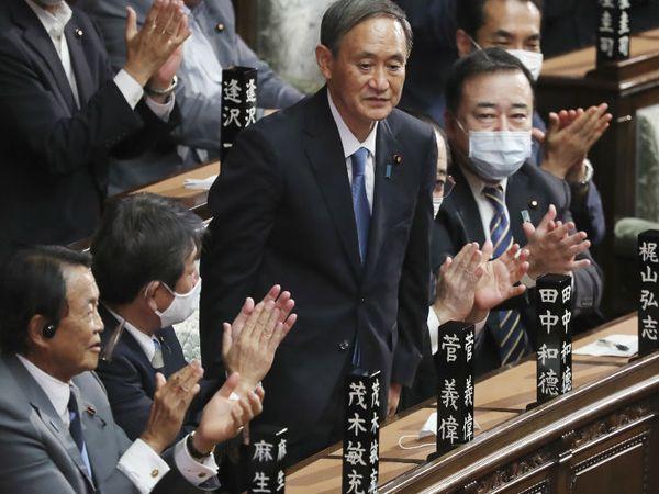 योशिहिडे सुगा (बीच में) को बुधवार को जापान का नया प्रधानमंत्री नियुक्त किए जाने के बाद ताली बजाकर बधाई देते सांसद। - Dainik Bhaskar