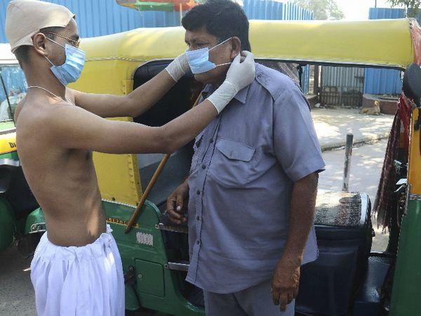 नई दिल्ली के कनॉट प्लेस पर गांधी जयंती के दिन प्रशासन ने कोरोना को लेकर जागरूकता कार्यक्रम गांधीगिरी टू मास्कगिरी चलाया। इस दौरान गांधी जी की वेशभूषा में युवक एक ऑटो ड्राइवर को मास्क पहनाते नजर आया। - Dainik Bhaskar