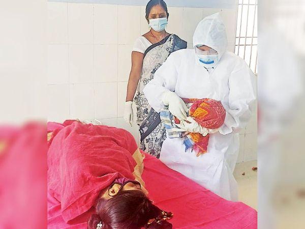 सुकून का भाव : सदर अस्पताल में कोरोना पॉजिटिव प्रसूता के सुरक्षित प्रसव के बाद पीपीई किट में नवजात को गोद में लिए खड़ी स्वास्थ्यकर्मी। - Dainik Bhaskar