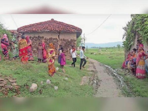 धराशायी दीवार को देखते ग्रामीण। - Dainik Bhaskar