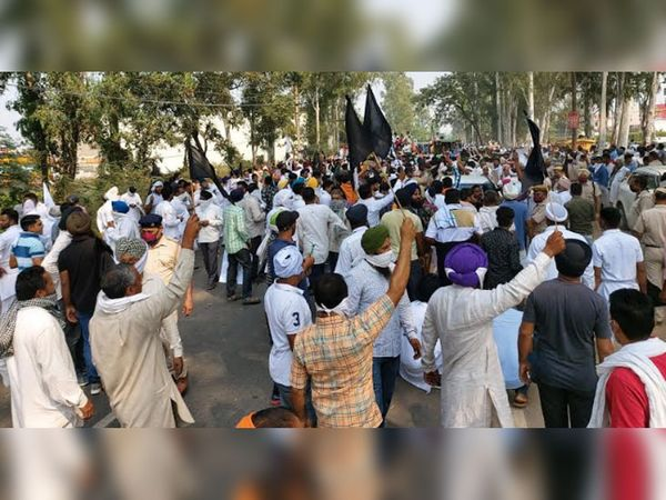 हाथों में काली झंडियां लेकर भाजपा नेताओं की ट्रैक्टर रैली का रास्ता रोके हुए किसान।