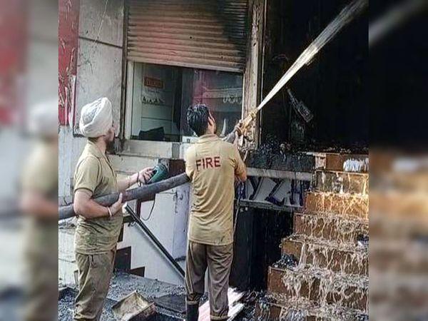 आग पर काबू पाने की कोशिश में पानी फेंकते फायर ब्रिगेड के कर्मचारी।