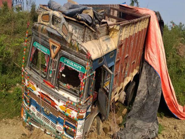 टायर फटने की वजह से ट्रक सड़क का बोल्डर तोड़ते हुए नीचे जाकर मिट्टी में धंस गई। काफी प्रयास के बाद ड्राइवर कोबचा लिया गया। - Dainik Bhaskar