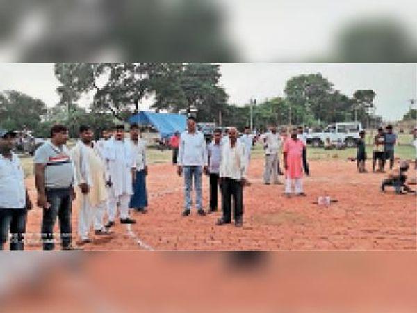 मुख्यमंत्री आगमन को लेकर हेलीपैड बनाते लोग। - Dainik Bhaskar
