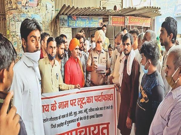 गोशाला संघ के सदस्य थाना प्रभारी को मांगों का ज्ञापन सौंपते ग्रामीण। - Dainik Bhaskar