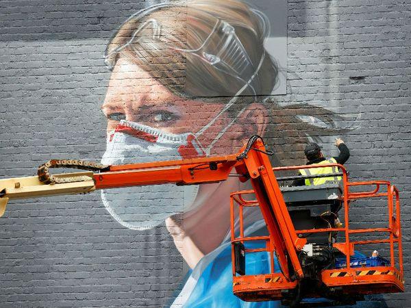 यह फोटो ब्रिटेन के मैनचेस्टर शहर की है। देश में कोरोनोवायरस का प्रकोप जारी है। इस बीच एक आर्टिस्ट दीवार पर मास्क पहने नर्स की फोटो बनाता नजर आया। यहां अब तक 7 लाख से ज्यादा संक्रमित मिल चुके हैं।