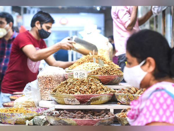 कोरोना महामारी के बीच फेस्टिव सीजन में बाजारों में लोगों की भीड़ बढ़ गई है। इसी बीच नई दिल्ली के चांदनी चौक पर एक युवक ड्राई फ्रूट्स खरीदता नजर आया। - Dainik Bhaskar