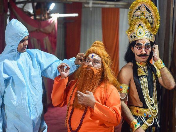 फोटो दिल्ली की है। यहां रामलीला के मंचन के लिए कलाकारों को पीपीई किट पहनकर तैयार करता मेकअप आर्टिस्ट। दिल्ली में अब तक 3.40 लाख से ज्यादा लोग संक्रमित हो चुके हैं। - Dainik Bhaskar
