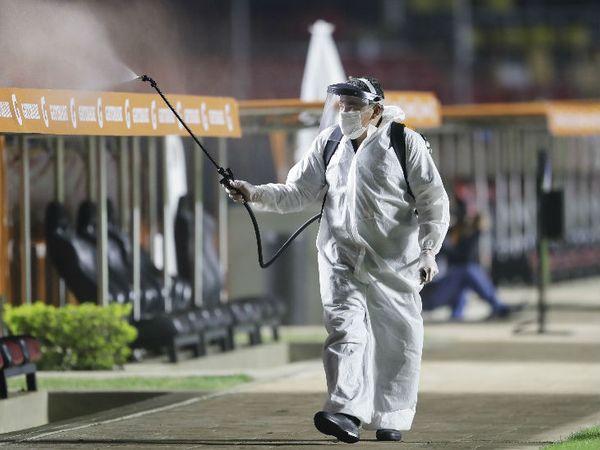 ब्राजील के साओ पाउलो में फूटबॉल मैच से पहले स्टेडियम को डिसइन्फेक्ट करता पीपीई किट पहना स्टाफ। - Dainik Bhaskar