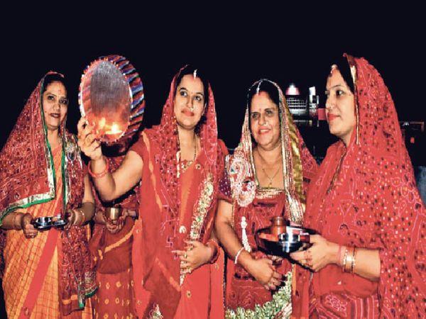 करवाचौथ पर पति की लंबी आयु के लिए चांद को देख व्रत पूरा करतीं महिलाएं। - Dainik Bhaskar