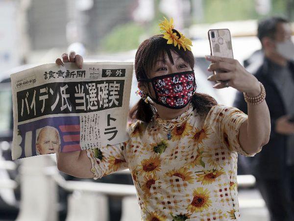 यह फोटो जापान की राजधानी टोक्यो का है। रविवार को यहां मास्क पहने एक महिला न्यूजपेपर के साथ सेल्फी लेते दिखी। अखबार में अमेरिका के राष्ट्रपति चुनाव में डेमोक्रेट के उम्मीदवार जो बाइडेन की जीत का जिक्र था। - Dainik Bhaskar
