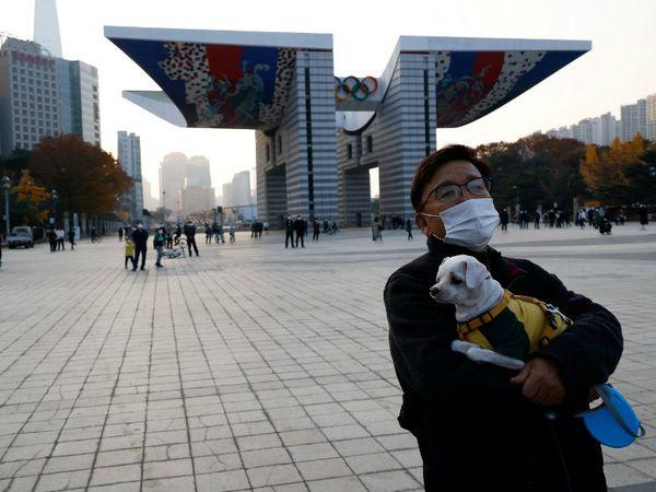 शनिवार को दक्षिण कोरिया के सियोल में अपने पपी के साथ एक व्यक्ति। देश में संक्रमण की तीसरी लहर शुरू हो चुकी है। सरकार ने फिर सख्त कदम उठाने की तरफ इशारा किया है।