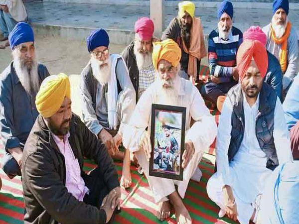 शहीद की फोटो के साथ पिता कुलवंत सिंह और शोक जताने पहुंचे ग्रामीण।