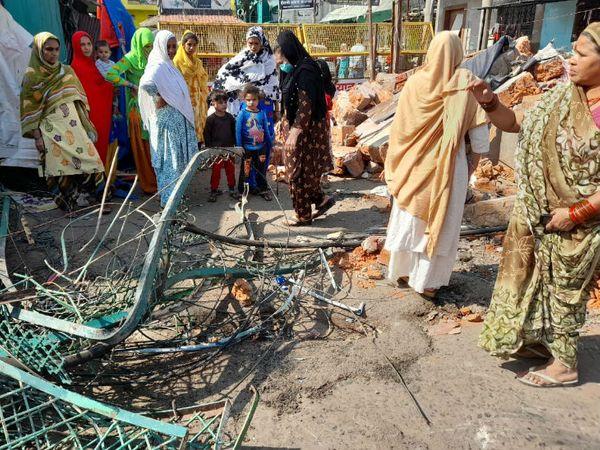 पुलिस की कार्रवाई रुकी तो महिला और बच्चे सामान उठाने में लग गए।