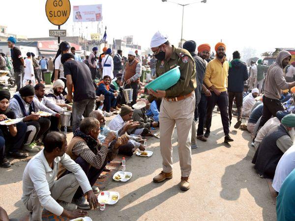 पुलिस के साथ किसानों के टकराव की तस्वीरों से यह फोटो अलग है। इसमें पंजाब पुलिस के सब इंस्पेक्टर बलविंदर सिंह किसानों को खाना परोस रहे हैं।