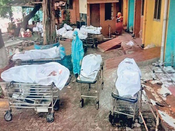तस्वीर अगस्त के महीने की रायपुर की है। यहां तेजी से बढ़ी कोरोना मरीजों की मौतों के बाद मॉरचुरी में शव रखने की जगह नहीं बचीं तो शवों को स्ट्रेचर पर बाहर निकाल कर खुले में रख दिया गया। स्थिति ऐसी हो गई कि अंतिम संस्कार के लिए श्मशान घाट पहुंची 10 लाशों को लौटाना पड़ गया। - Dainik Bhaskar