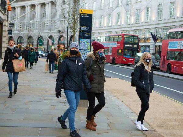 मंगलवार को लंदन की एक सड़क से गुजरते लोग। ब्रिटेन सरकार के चीफ साइंस एडवाइजर ने लोगों से कहा है कि वैक्सीन आने का यह मतलब नहीं है कि वे लापरवाह हो जाएं।
