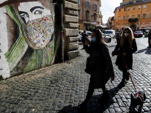 इटली के रोम में मंगलवार को एक वॉल पेंटिंग के सामने से गुजरती महिलाएं। देश में मरने वालों का आंकड़ा 60 हजार से ज्यादा हो गया है। सरकार ने यहां लोगों से मास्क लगाने के मामले में लापरवाही न बरतने को कहा है।