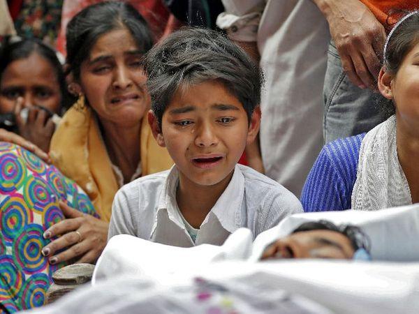फरवरी 2020 में दिल्ली में CAA के खिलाफ प्रदर्शन के दौरान हिंसा भड़क उठी। इसमें मुदस्सिर खान की भी मौत हुई। फोटो मुदस्सिर के शव के पास बैठे उनके बेटे की है।