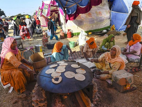 फोटो सिंघु बॉर्डर की है। रविवार को यहां प्रदर्शनकारी किसानों के लिए खाना बनाती हुई महिलाएं।