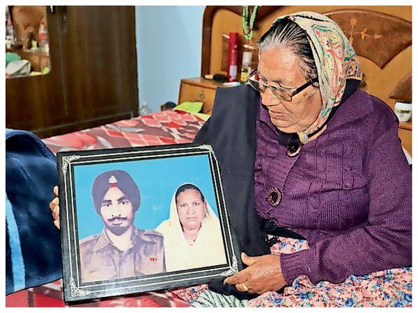 फ्रेम में तस्वीर मंगल सिंह की है। यह 1971 में खींची गई थी। उसी फोटो को निहारतीं पत्नी सत्या देवी। - Dainik Bhaskar