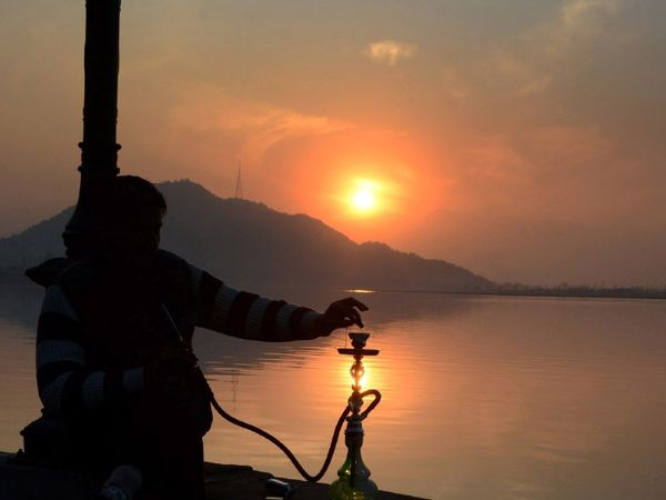 फोटो श्रीनगर डल झील की है। यहां साल के आखिरी दिन सूर्यास्त का नजारा देखते हुए स्थानीय नागरिक।