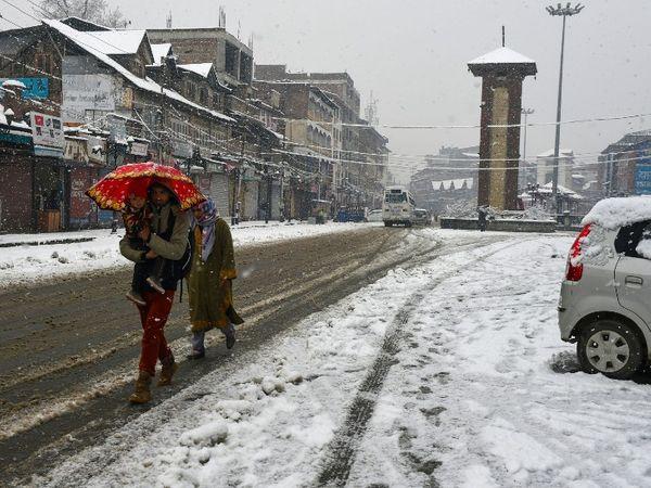 श्रीनगर में सड़कों पर जमी बर्फ के बीच से गुजरते लोग। फोटो रविवार की है।