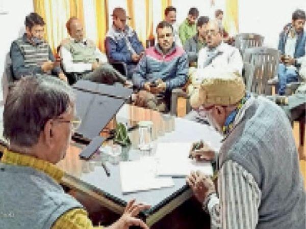 उपज को लेकर हुई बैठक में चर्चा करते मंडी के प्रभारी सचिव और व्यापारी। - Dainik Bhaskar