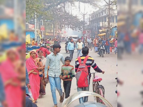 मौसम में आई गर्माहट के कारण सड़क पर धूप का आनंद लेते हुए लोग। - Dainik Bhaskar