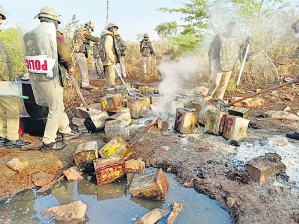 शराब नष्ट कराती पुलिस टीम। - Dainik Bhaskar