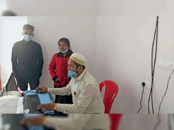 जिला अस्पताल के बी-ब्लॉक में मेडिकल कॉलेज के टीकाकरण केंद्र का सिस्टम स्लो हो गया। इसे सुधरने के लिए मैकेनिक को बुलाया गया। - Dainik Bhaskar