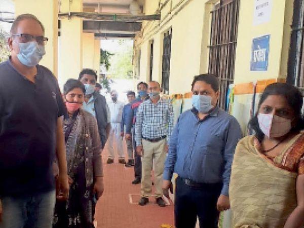 होशंगाबाद। जिला अस्पताल में टीकाकरण के लिए सोशल डिस्टेंसिंग में खड़े स्वास्थ्य कर्मचारी। - Dainik Bhaskar