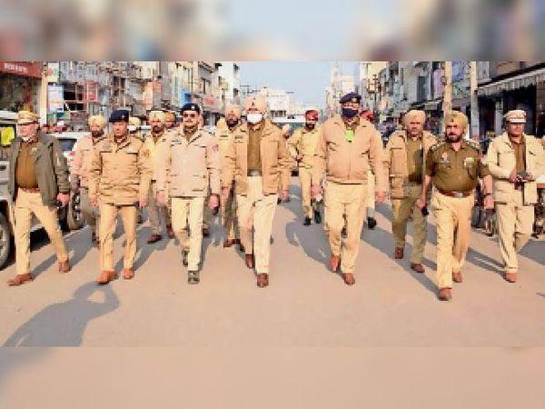शहर में फ्लैग मार्च करते पुलिस के अधिकारी और मुलाजिम। -भास्कर - Dainik Bhaskar