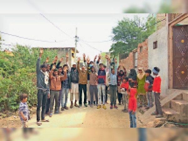 हिंडौन सिटी| गुलशन कॉलोनी में 33 केबी बिजली लाइन काफी नीचे से निकल रही है। लाइन गिरने से हादसे का भय बना रहता है। बिजली लाइन हटवाए जाने की मांग को लेकर प्रदर्शन करते लोग। - Dainik Bhaskar