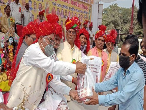घड़ी चौक पर आयोजित कार्यक्रम में लोगों को प्रसादी के रूप में सब्जियाें के पैकेट देते पदाधिकारी। - Dainik Bhaskar