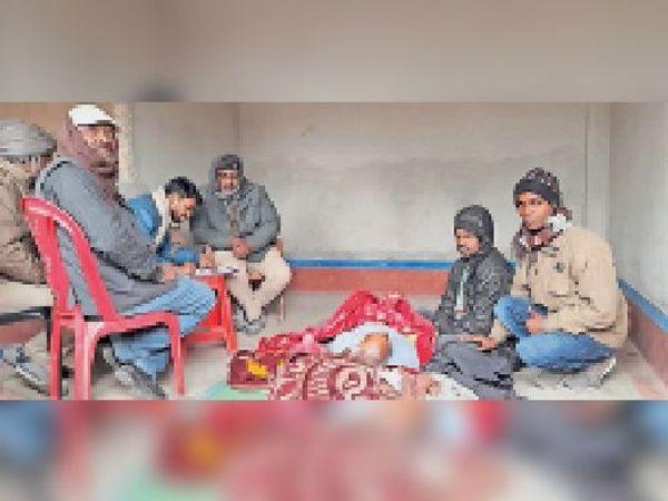 मृतक के पास बैठे परिजन से पूछताछ करती पुलिस। - Dainik Bhaskar